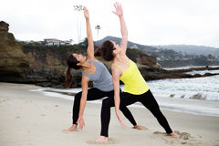 Two beautiful women practicing yoga at beach Stock Image