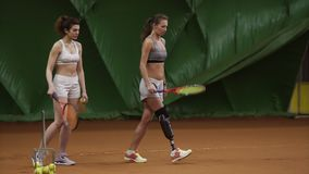 Two beautiful women with rackets in their hands are preparing for the start tennis game . One woman with a prosthesis on. Her leg. Indoors stock footage