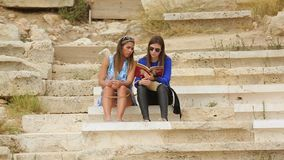 Two beautiful women reading tourist guide, planning sightseeing tour together. Stock footage stock video