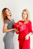 Two beautiful women with red gift box Stock Photos