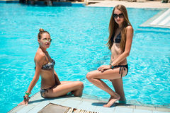 Two beautiful women relaxing near swimming pool Royalty Free Stock Image