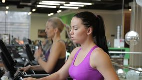 The two beautiful women are running on the treadmill in modern gym. The sportswoman with balck head and in purple sport bra stops her machine and finishes her stock video footage