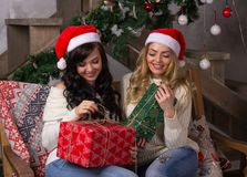 Two beautiful women in santa hats smiles unfold gifts for Christ. Two beautiful girls in santa hats smiles unfold gifts for Christmas. Two beautiful women sits a Royalty Free Stock Image