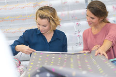 Two beautiful women selecting tissue at fabric shop Royalty Free Stock Photo