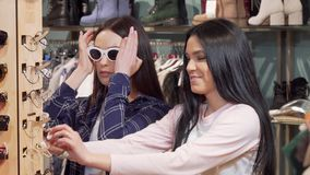 Two beautiful young women shopping for sunglasses together. Two beautiful women shopping for sunglasses. Attractive female friends having fun at fashion store stock footage