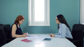 Two beautiful women sign contract at office. At the left the red haired woman is dressed darkly sapphire chiffon blouse. She looks through papers and then stock video footage