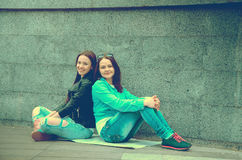 Two beautiful women sits on the street. Looking at the camera and smiling Royalty Free Stock Photography