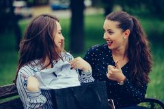 Two beautiful women sitting on the park bench after shopping and sharing their new purchases with each other royalty free stock images