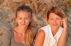 Two beautiful women sitting on sand at the beach look at the sunset Royalty Free Stock Photos