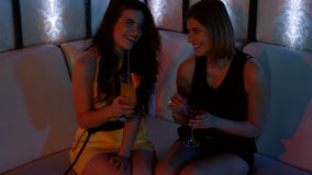 Two beautiful women sitting on sofa and having cocktail. In the bar 4K stock video