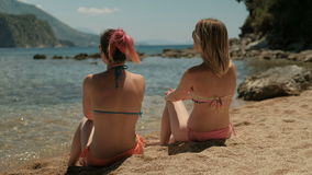 Two beautiful women are sitting on a sunny beach and talking. Attractive ladies rest on the sand. stock video footage