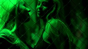 Two beautiful women standing behind chain fence, smiling seductively, passion stock images