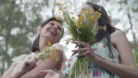 Two beautiful women standing in the forest with amazing wild flowers. Slow motion.