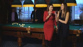 Two beautiful women standing near a pool table talking to two men in the background playing pool. Two beautiful women in evening dresses stood next to the pool stock footage