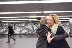 Two beautiful women standing at the underground platform, huggin Royalty Free Stock Image