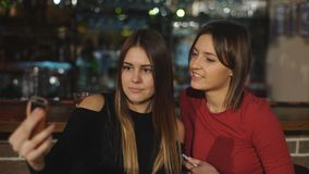 Two beautiful women take a selfie at the bar. Two beautiful brunette women take a selfie at the bar,two girls Hamming for the camera stock video