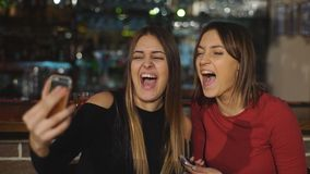 Two beautiful women take a selfie at the bar. Two beautiful brunette women take a selfie at the bar,two girls Hamming for the camera stock footage