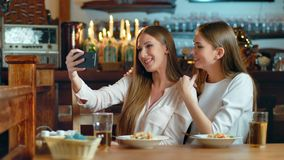 Two beautiful women taking selfie in cafe.  stock footage