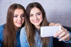 Two beautiful women taking selfie photo with smart phone stock photos