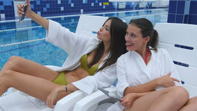 Two beautiful women taking selfies lying on chaise longues near the swimming pool.