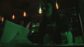 Two beautiful women talking in a bar and drinking a cocktail. 4K UHD stock footage