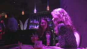 Two beautiful women talking in a bar and drinking a cocktail. 4K UHD stock video footage