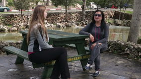 Two beautiful women talking to each other, sitting on a park bench stock video footage