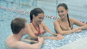 Two beautiful women talking to a young man in the swimming pool stock footage
