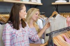Two beautiful women touching a shirt Royalty Free Stock Photography
