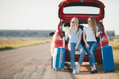 Two beautiful women are traveling on a red car stock photos