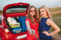 Two beautiful women are traveling on a red car Royalty Free Stock Image
