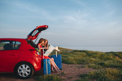 Two beautiful women are traveling on a red car Royalty Free Stock Photography