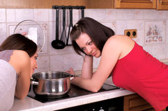 Two beautiful women trying to cook Stock Images