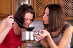 Two beautiful women trying to cook Royalty Free Stock Photo