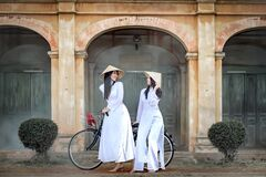 Two beautiful women in Vietnam`s national costume Riding a bicycle to see ancient buildings