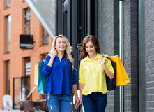Two beautiful women walking holding hands with shopping bags Stock Photography