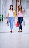 Two beautiful women walking in mall with shopping bags stock image