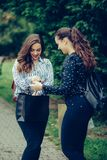 Two beautiful women walking in the park after shopping and sharing their new purchases with each other stock photography