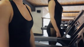 Two beautiful women work out on racetracks in gym, close up. Treadmill is exercise machine for run indoors. Correctly using it is possible to increase stock video