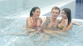 Two beautiful women and a young man taking selfies in the swimming pool stock video