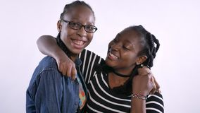 Two beautiful young african women hugging and laughing, looking at camera, happy and emotional, white studio background.  stock footage