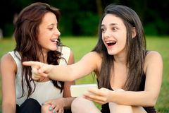 Two beautiful young amazed women pointing outside Stock Photo