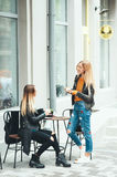 Two beautiful young blonde girls drinking coffee and talking near the cafe Royalty Free Stock Photography