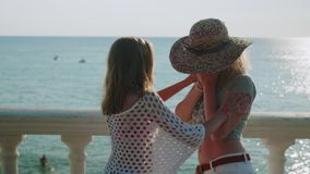 Two beautiful young blondes on the beach at sunset. One cries. Another calms her down. In backlight stock video