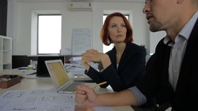 Two beautiful young businessman talking on the. Businessman and Businesswoman beautiful with red hair, sitting at their jobs and talking about a new interesting stock footage