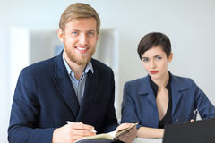 Two beautiful young businesspeople sitting in office and smiling Stock Images