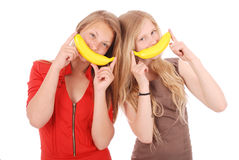 Two beautiful young caucasian girl with banana smile Royalty Free Stock Photos