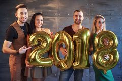 Two beautiful young couples having fun at New Year`s Eve Party, holding cardboard numbers 2018 Royalty Free Stock Images