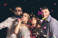 Friends blowing party whistles stock photography