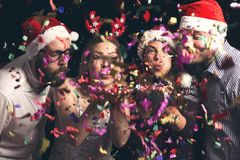 Friends blowing away colorful confetti stock photos